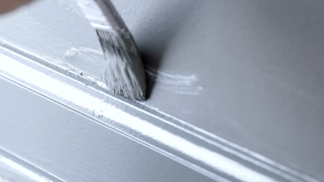Detail of painting bottom of gray wall with brush video