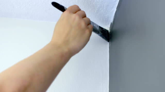 Detail of painting top corner of gray wall with brush video