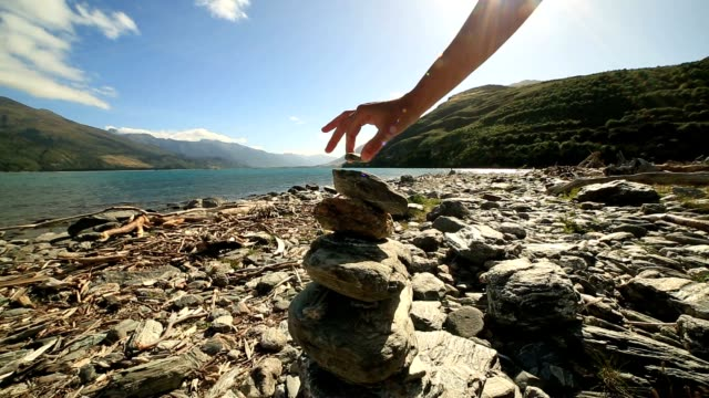 Detail of person stacking rocks by the lake at sunrise video