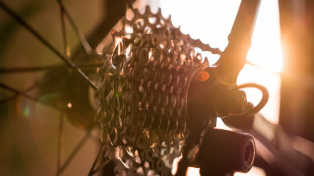 Detail of spinning derailleur gears and bike wheel spokes at sunset video