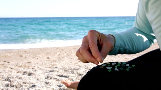 Detail of woman sifting through sandy beach, finding gems video