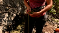 Detail of woman tying into climbing rope, arranging gear video