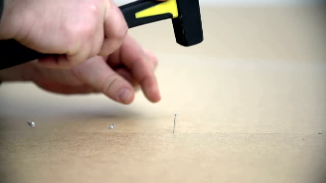Detail shot of hammering down a tiny nail into the closet's plate video