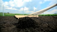 Detail shot of rake moving earth in slow motion video