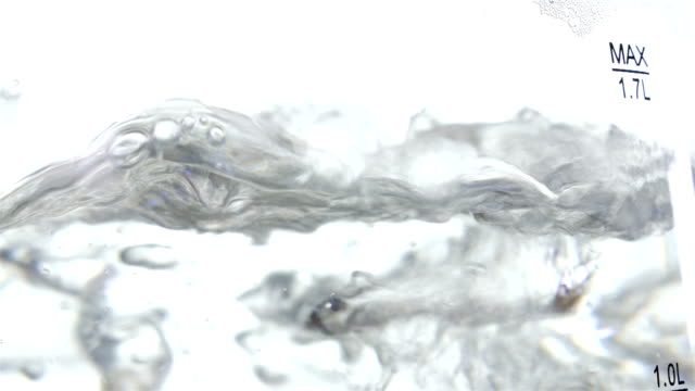 Detail shot of water boiling with bubbles in electric kettle, 4k video