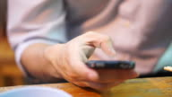Detail view of Hand using smartphone at restaurant video