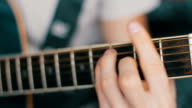 Details of performer man hands playing acoustic guitar musical, vintage retro photo video