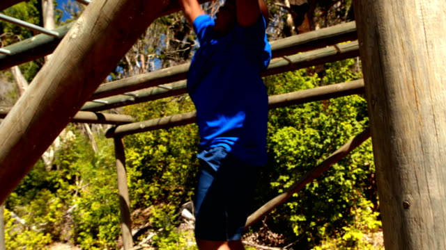 Determined boy exercising on monkey bar during obstacle course video