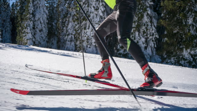 Determined cross country skier skate skiing uphill alongside a forest video