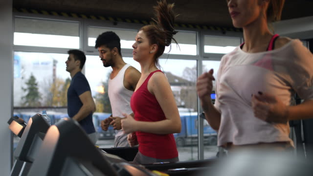 Determined young people running on treadmill in a gym. video