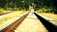 A devil-may-care young man walks along the railroad and plays the guitar video