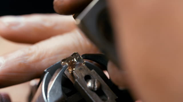 A diamond is polished by a skilled worker in the diamond processing center video