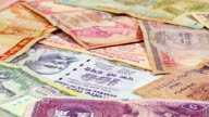 Different asian currency bank notes rotating business background video