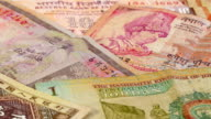 Different asian currency banknotes rotating and panning background video