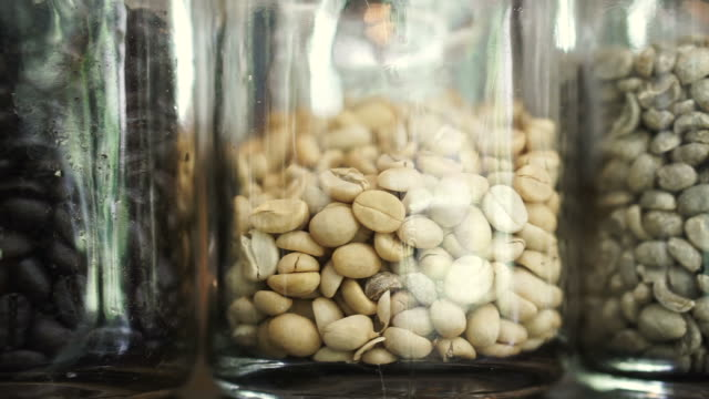 Different levels of roasted coffee beans in glass jar, light, medium and dark roast video