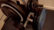 Different weights for the barbell in the rack in a gym video