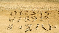 Digits & signs written on a beach sand. video