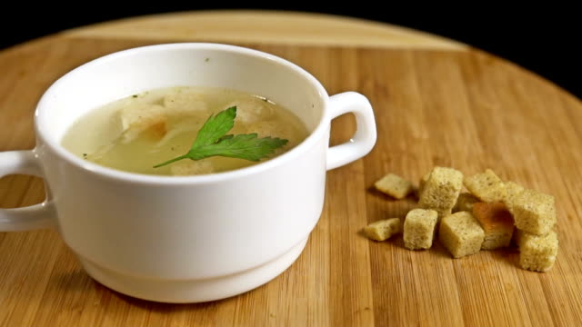 dill falls into chicken soup with croutons. Slow motion video