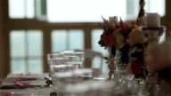 Dinnerware arrangement of festive table close up macro changing rack focus. Wedding reception banquet table set with glassware cutlery flowers in vases and candles decor details and ready for guests video