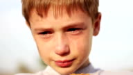 dirty orphan boy close-up crying and looking at camera on the background of the ruins video