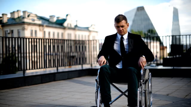 Disabled businessman trying to get up from wheelchair outdoor video