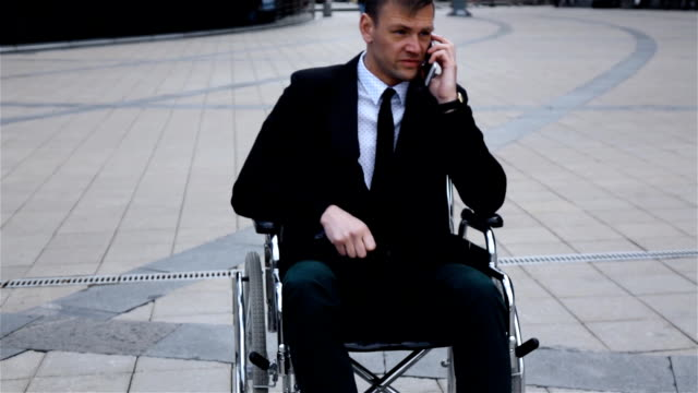Disabled Invalid businessman talking by phone video