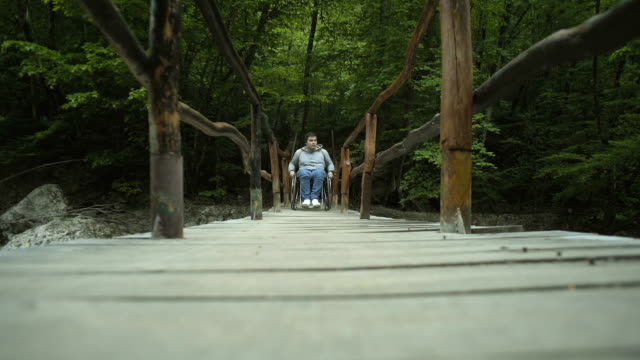 Disabled Man In Wheelchair On A Wooden Bridge video