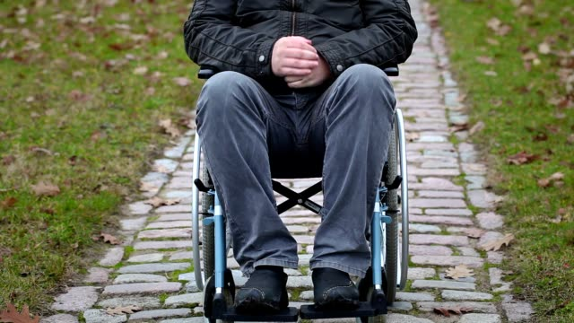 Disabled man sitting on wheelchair at outdoor video