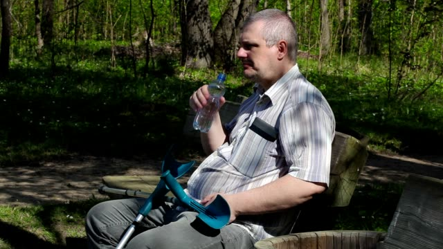 Disabled man with crutches sitting on the bench and drinking water video