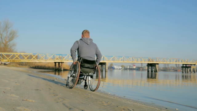 disabled person, back view, handicapped goes to embankment along video