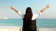 Disabled woman with arms outstretched at the beach video
