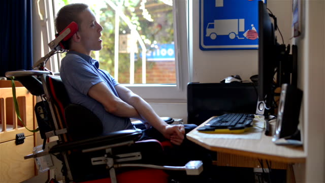 Disabled young man using computer video