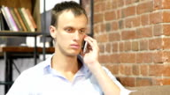 Disappointed, Unhappy, sad man talking on cellphone at creative work place video