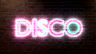 Disco logo neon lights sign on brick wall text glowing multicolor video