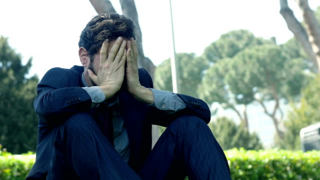 discomforted businessman sitting on the grass in a public park: sad businessman video