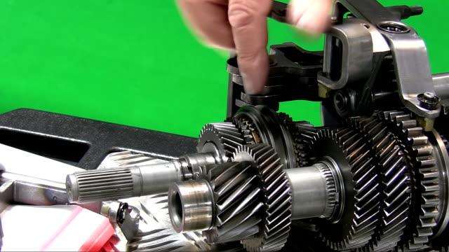 Dismantling car gearbox. Teacher showing parts video