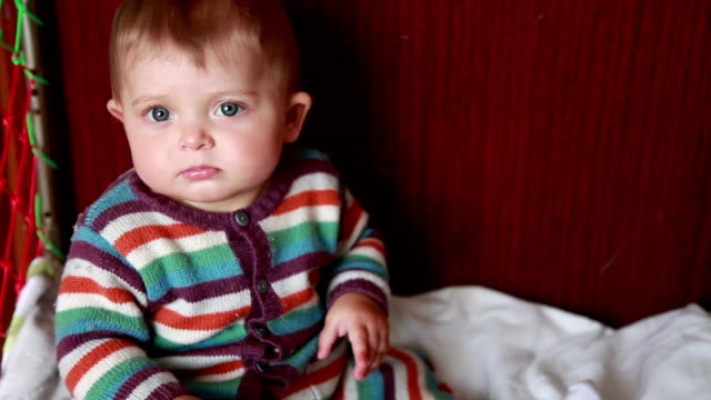Displeased baby looking at camera and frowning video