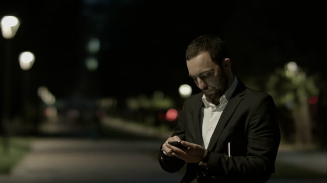 Displeased bearded businessman use smart phone, while standing in the city street,business man reading messages,  brunette using cell phone at evening outdoors, park video