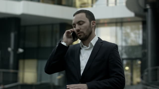 Displeased business man seriously talking by phone, standing outside the office video
