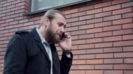 Distracted businessman pulling out his mobile video