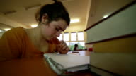 Distressed young girl working in library video