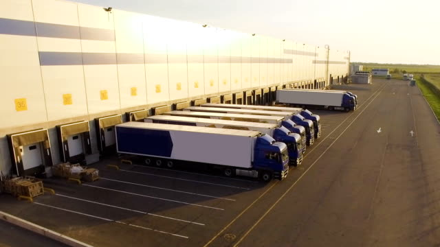 distribution warehouse with trucks awaiting loading video
