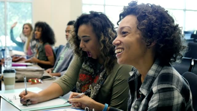 Diverse female college students take notes during lecture video