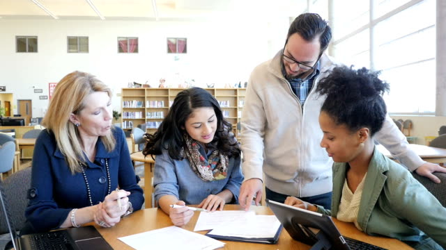 Diverse group of adult college students studying together in library during tutoring session video