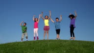 Diverse group of kids jumping on hill in slow motion video
