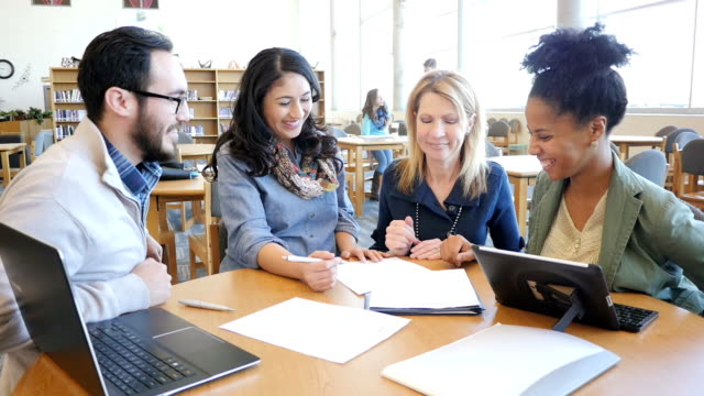Diverse group of mature and mid adult college students studying for continuing education class in library video
