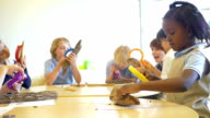 Diverse group of private school children studying nature with magnifying glasses in science class video