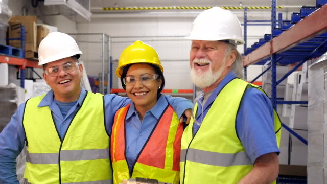 Diverse group of shipping & distribution warehouse employees smiling together video
