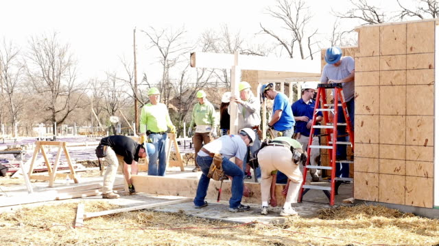 Diverse group of volunteers raise beam on home for charity video