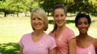 Diverse happy women wearing pink for breast cancer awareness video